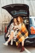 """Постер, картина, фотообои """"смех взрослых женщин, завернутые в одеяла, держа бутылки соды, сидя в багажнике на городской улице"""""""