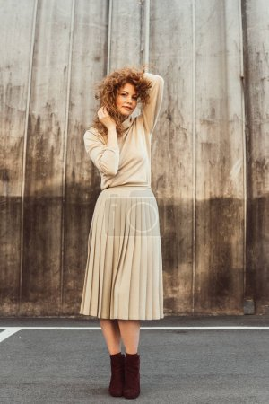 stylish curly redhead woman in beige turtle neck and skirt posing at city street