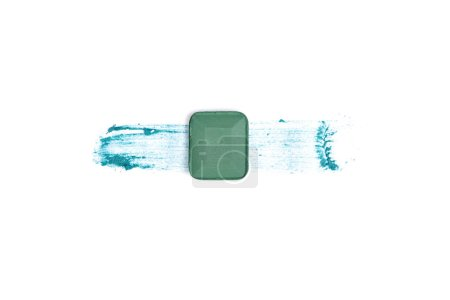 top view of eyeshadow of green color with stroke on white background