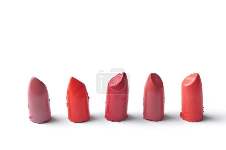 close up view of cut lipsticks on different colors on white backdrop