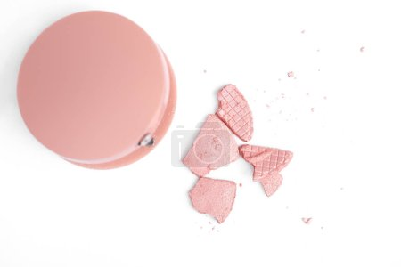 top view of cracked pink blush and container isolated on white
