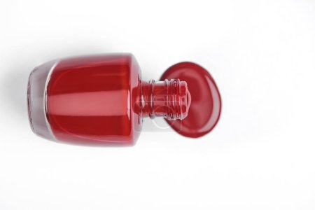 top view of red nail polish and bottle on white background