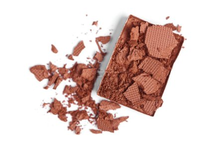 top view of cracked brown eyeshadow on white backdrop