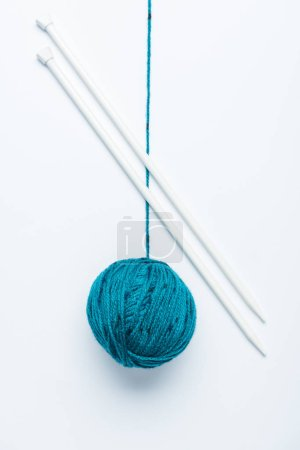 top view of blue yarn ball  and knitting needles on white background
