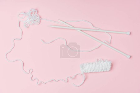 flat lay with white yarn and knitting neeldes on pink backdrop