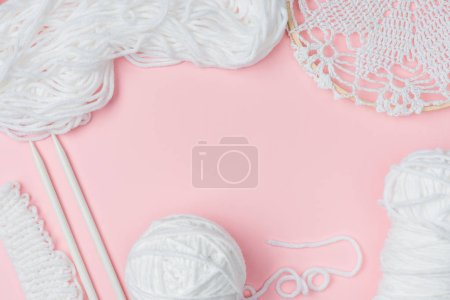 top view of white yarn and knitting needles on pink backdrop