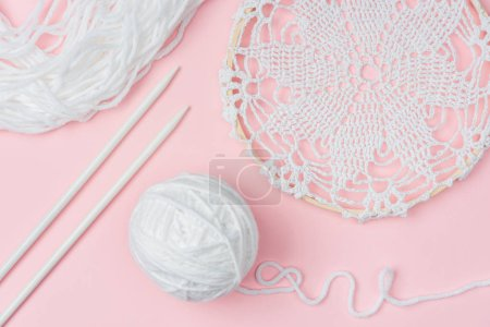 flat lay with white yarn and knitting needles on pink backdrop