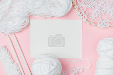 flat lay with white yarn, knitting needles and blank paper on pink background
