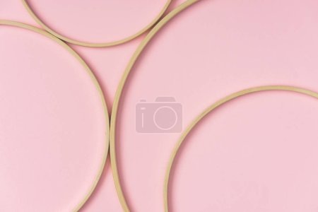 flat lay with wooden embroidery hoops arranged on pink background