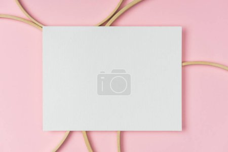 flat lay with wooden embroidery hoops and blank paper arranged on pink background