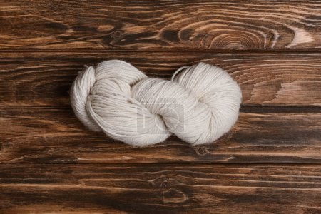 top view of white yarn clew for knitting on wooden surface