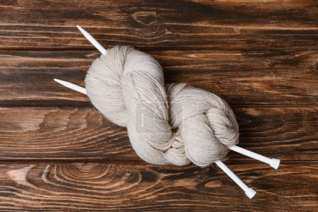 top view of white yarn clew with knitting needles on wooden tabletop