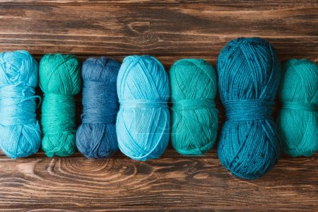 Photo for Top view of green and blue knitting yarn clews on wooden surface - Royalty Free Image