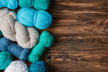 flat lay with arranged blue, white and green yarn clews on wooden tabletop