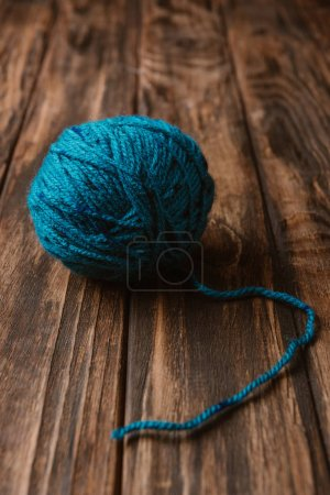 close up view of blue yarn clew on wooden tabletop