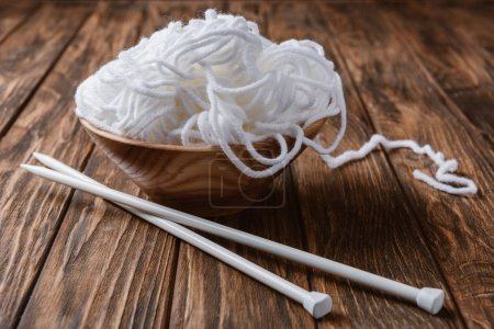 Photo for Close up view of white yarn in bowl and knitting needles on wooden tabletop - Royalty Free Image
