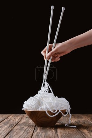 cropped shot of woman holding white yarn with knitting needles like noodles on wooden tabletop on black background