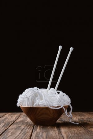 close up view of white yarn in bowl and knitting needles on wooden surface on black backdrop