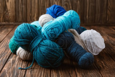 close up view of white, blue and green yarn for knitting on wooden surface