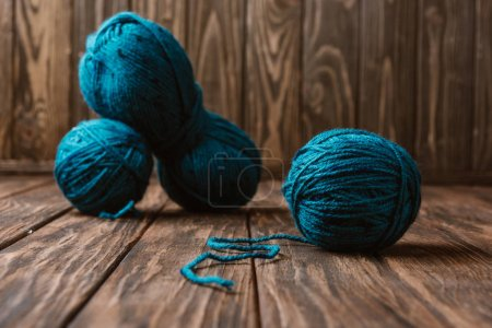 close up view of blue yarn for knitting arranged on wooden surface