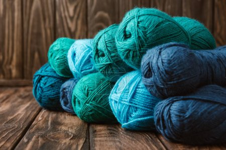 close up view of blue and green yarn clews on wooden surface