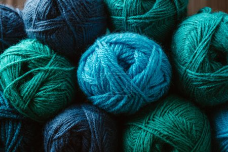 full frame of blue and green yarn balls for knitting as background