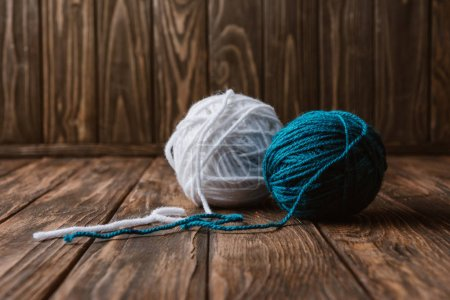 Photo for Close up view of white and blue yarn balls on wooden tabletop - Royalty Free Image