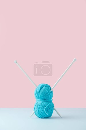 close up view of blue yarn clew and knitting needles on pink and blue background