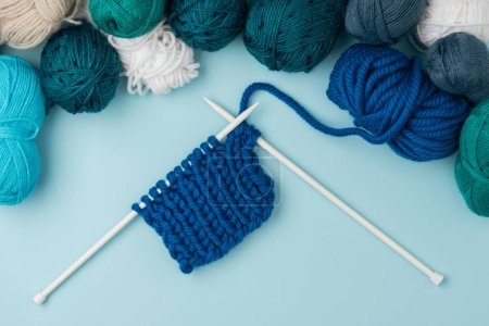top view of arranged yarn clews and white knitting needles on blue background