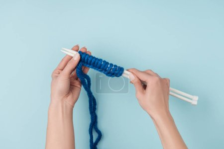 partial view of woman with blue yarn and white knitting needles knitting on blue backdrop