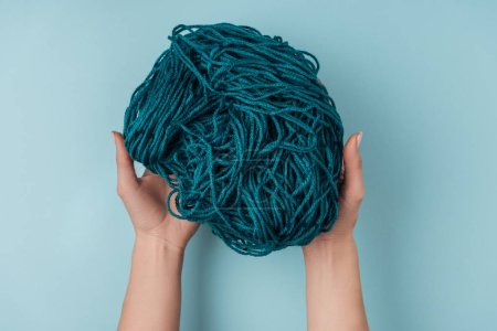 partial view of woman holding yarn for knitting in hands on blue backdrop