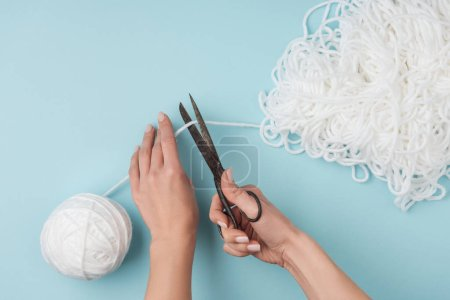 cropped shot of woman cutting white knitting thread with scissors on blue backdrop