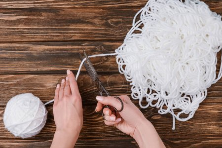 partial view of woman cutting white knitting thread with scissors on wooden surface