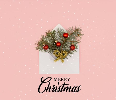 "top view of white envelope with fir twigs and shiny christmas baubles isolated on pink with ""merry christmas"" lettering and snow"