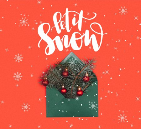 """close-up view of green envelope with fir twigs and shiny christmas baubles isolated on red with """"let it snow"""" lettering and snowflakes"""