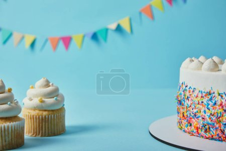 Tasty cupcakes and cake on blue background with bunting