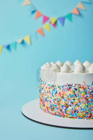 Delicious cake with sugar sprinkles and meringues on blue background