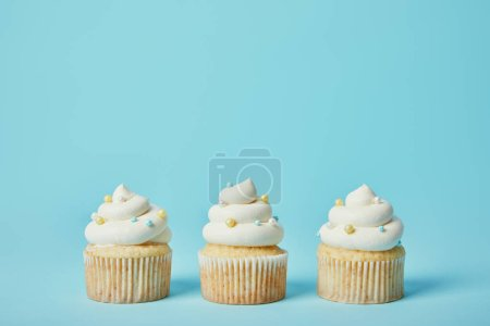 Tasty cupcakes with sugar sprinkles on blue backgr...