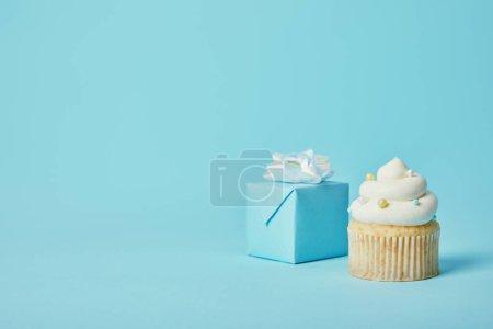 Coffret cadeau avec arc blanc et délicieux cupcake sur fond bleu