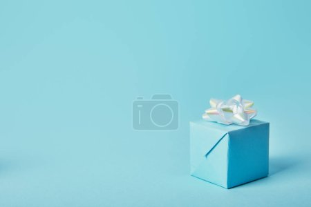 Gift box with white bow on blue background