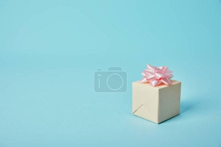Gift box with pink bow on blue background
