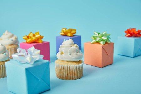 Délicieux cupcakes et cadeaux colorés sur fond bleu