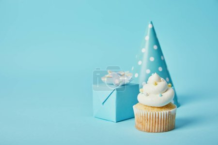 Photo for Party hat, gift box and delicious cupcake on blue background - Royalty Free Image