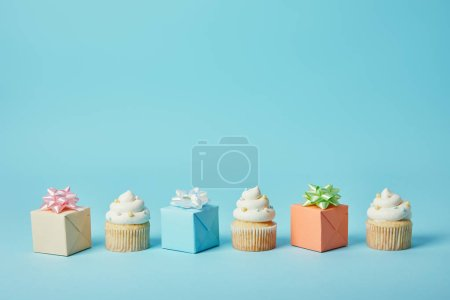 Delicious cupcakes and diffrent gifts on blue background