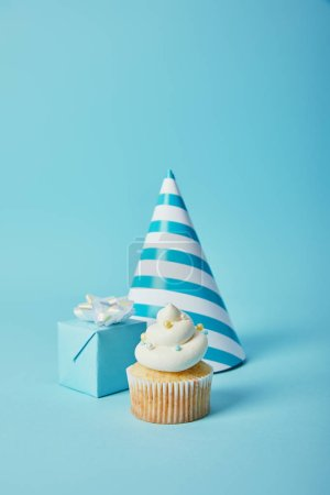 party hat, gift box and tasty cupcake with sugar sprinkles on blue background