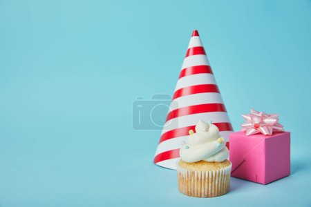 Red white party hat, pink gift box and delicious cupcake on blue background