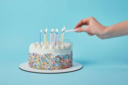 Photo for Partial view of woman lighting candles on birthday cake on blue background - Royalty Free Image