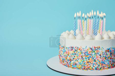 Photo for Delicious Birthday cake with lighting candles on blue background - Royalty Free Image