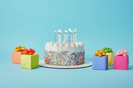 Photo for Delicious cake with candles, colorful gifts and confetti on blue background - Royalty Free Image