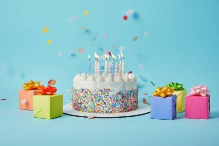 Foto de Sabrosa tarta con velas, regalos de colores y confeti sobre fondo azul - Imagen libre de derechos